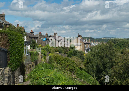 View under blue sky along row of stone houses (semis) situated at top of Baildon Bank, a steep wooded cliff - Shipley, - Stock Photo