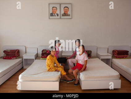 North Korean girls in a room under the official portraits of the Dear Leaders in Songdowon international children's - Stock Photo