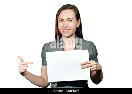 the girl on a white background holds in her hand a white plate without inscriptions and points to it with her finger, - Stock Photo