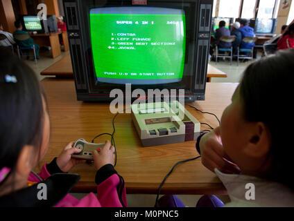 North Korean children playing video games in Songdowon international children's camp, Kangwon Province, Wonsan, - Stock Photo