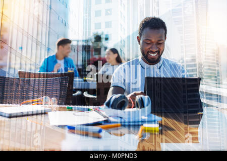 Smiling afro-american man working on his tablet - Stock Photo