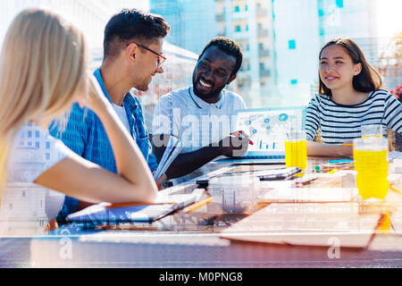Happy afro-american man discussing work with his co-workers - Stock Photo