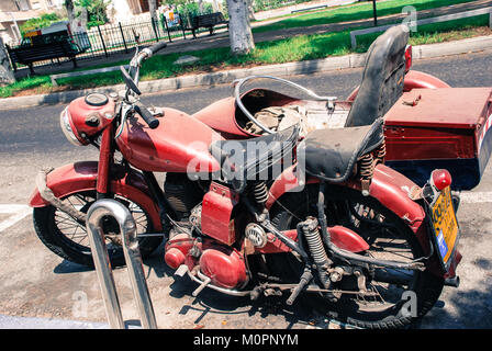 TEL AVIV, ISRAEL - AUGUST 18, 2010: Horizontal picture of old red motorcycle parked in the streets of Tel Aviv, - Stock Photo