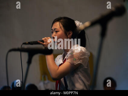 North Korean pioneer girl singing during a show for tourists, Pyongan Province, Pyongyang, North Korea - Stock Photo