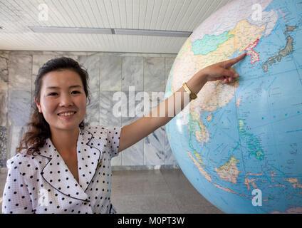 Female guide showing North Korea on a globe at Songdowon international children's camp, Kangwon Province, Wonsan, - Stock Photo