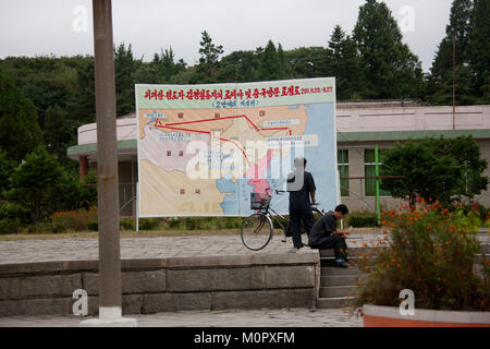 North Korean men in front of the map of the last Kim Jong il trips in train, North Hwanghae Province, Kaesong, North - Stock Photo