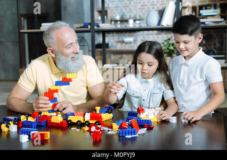 Joyful family playing with building block at home - Stock Photo