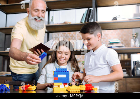 Loving grandfather helping kids with house construction - Stock Photo