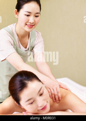 young asian masseur performing massage on woman in spa salon. - Stock Photo