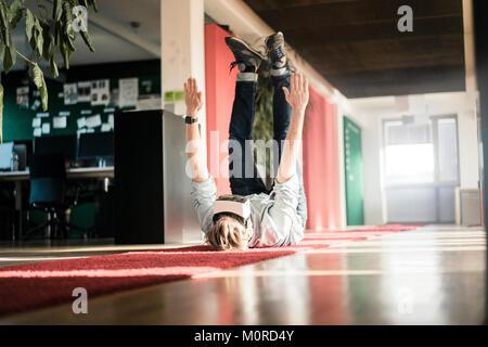 Businessman lying on carpet on the floor wearing VR glasses exercising - Stock Photo