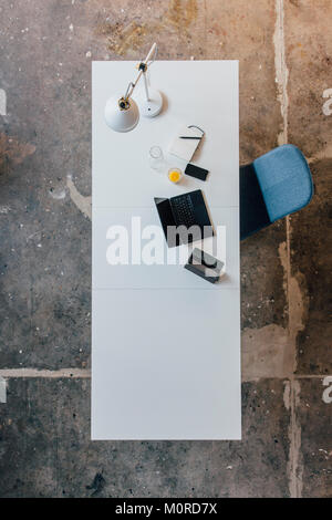Desk seen from above, tablet, smartphone, laptop, orange juice and notebook - Stock Photo