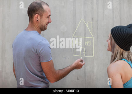 Man and woman drawing a house with chalk on concrete wall - Stock Photo