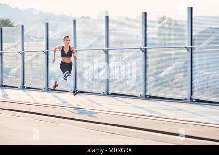 Young woman running in the city - Stock Photo