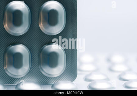 Macro shot detail of tablet pills in silver aluminium blister pack packaging on blurred background of pack of pills - Stock Photo