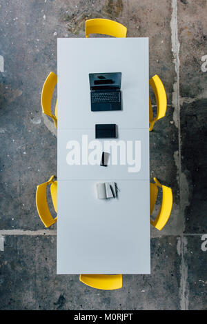 Conference table seen from above, tablet, smartphone, laptop and notebook - Stock Photo