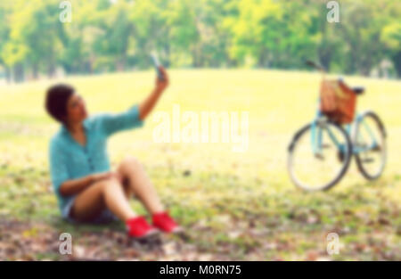 Beautiful young woman using a moblie phone in a park. Portrait, Style image blur - Stock Photo