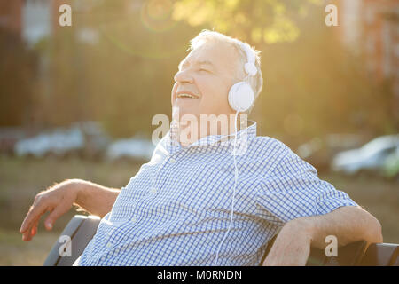 Outdoor portrait of senior man who is listening music on headphones. - Stock Photo