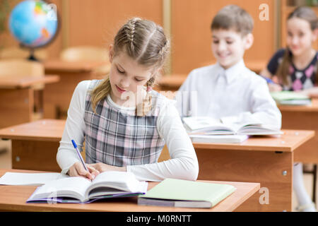 Education, school, learning and children concept - group of school kids with pens and textbooks writing test in - Stock Photo