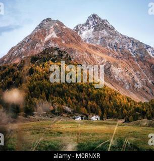 Small houses in Maloja village against mountain at sunset in autumn, Maloja Pass, Switzerland. - Stock Photo
