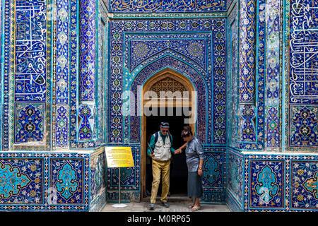 Two Tourists Visiting The Shirin Beka Oka Mausoleum, The Shah-i-Zinda Mausoleum Complex, Samarkand, Uzbekistan - Stock Photo