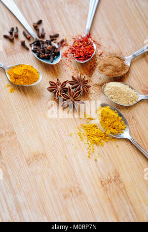 Colorful spices on a wooden background - Stock Photo