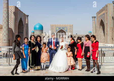A Wedding Party Poses For Photos At The Registan Complex, Samarkand, Uzbekistan - Stock Photo