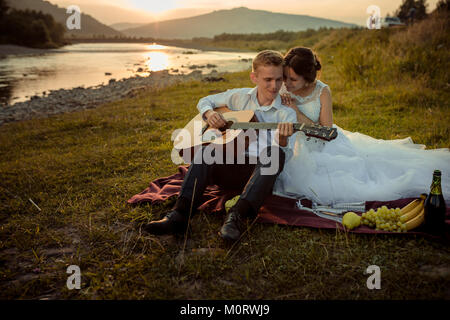 Romantic wedding portrait during the sunset. Handsome groom is playing the guitar and the gorgeous bride hugging - Stock Photo