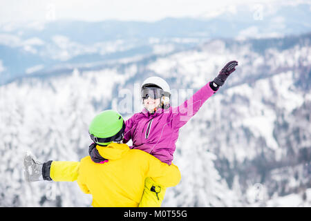 Couple in sports clothes during the winter vacation on the mountains - Stock Photo