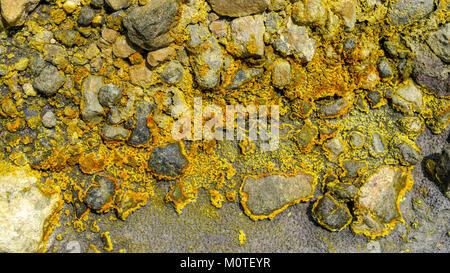 Sulfur sulphur deposits on the side of a tiny stream in the caldera.  White Island / Whakaarian Volcano, Bay of - Stock Photo