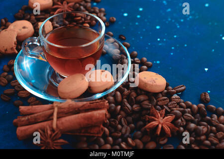 Close-up of a glass espresso cup with coffee beans, cinnamon, spices and cookies. Dark food photography with copy - Stock Photo