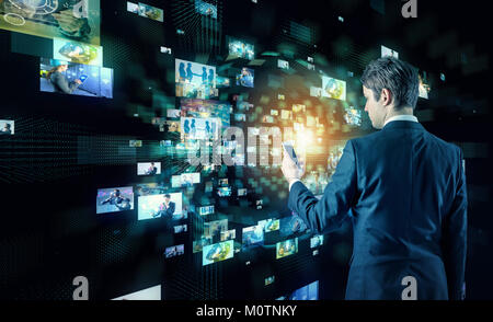 Young business man watching many pictures with smart phone. - Stock Photo