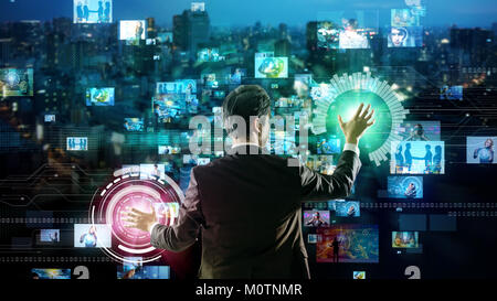 Young man using futuristic graphical user interface. - Stock Photo