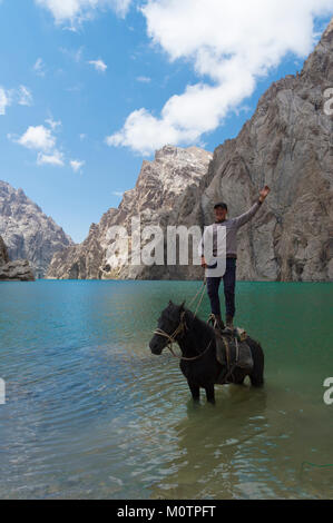 Kyrgyz showing his agility on his horse in Köl-Suu lake, Kurumduk valley, Naryn province, Kyrgyzstan, Central Asia - Stock Photo