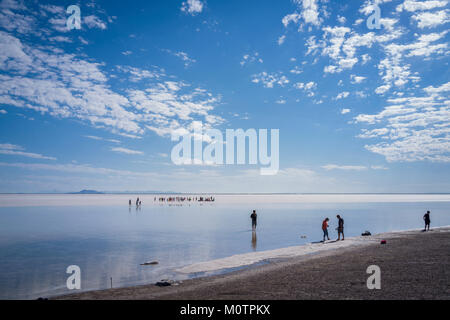 Tourists walk in inches deep salt water near Bonneville Salt Flats, Wendover, Utah - Stock Photo