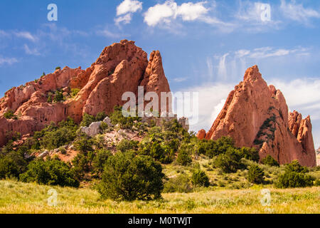 View of the amazing Garden of the Gods Park in Colorado Spring, Colorado; green grass, trees and bushes in the foreground; - Stock Photo