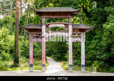 The old wooden chinese gate in the garden of tropical agronomy in Paris has lost its original red color because - Stock Photo