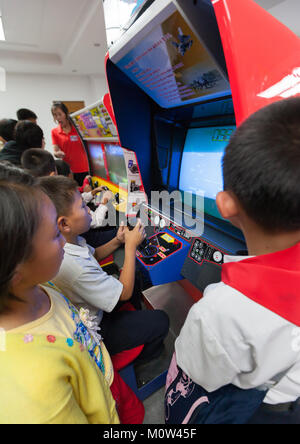 North Korean child on a car simulator in Kaeson youth park, Pyongan Province, Pyongyang, North Korea - Stock Photo