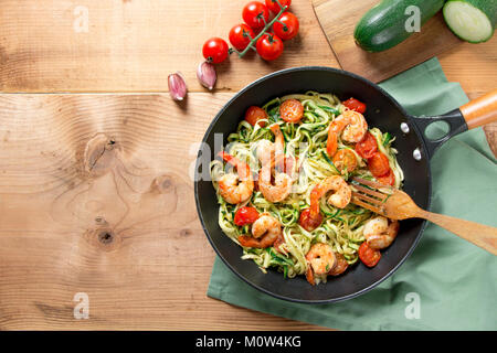 Zucchini spaghetti sauteed with tomato cherry and prawns in a pan on a rustic wooden table. Top view - Stock Photo
