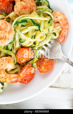 Zucchini noodles sauteed with tomato cherry and prawns in a dish on a rustic white wooden table. Close up - Stock Photo