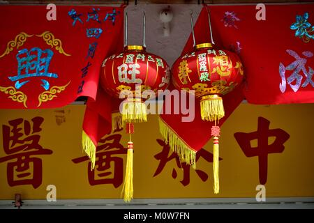 Red and gold lanterns with banners celebrating Chinese Lunar New Year in Geylang, Singapore - Stock Photo