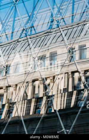 Reflections of old building in modern architecture glass facade. - Stock Photo