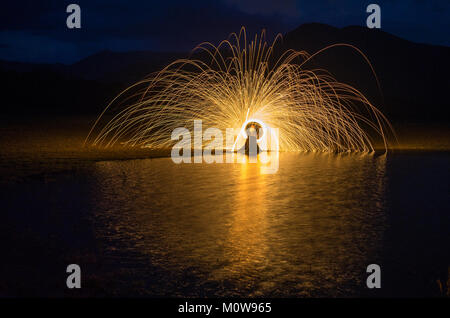 Ring of fire on the lake at night with mountain background. - Stock Photo
