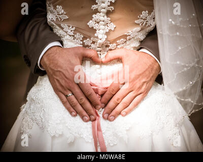 The groom creating heart shape with his hands on the back of the bride.Couple in love. Close up of hands. Young - Stock Photo