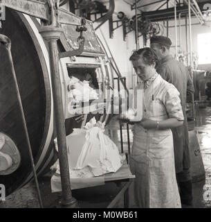 1950s, historical, a female worker checks the butter produced from a large cylindrical wooden drum at a small creamery - Stock Photo