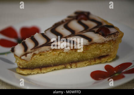 close up macro food photography of a slice of home made Bakewell tart or cake on a red floral plate with chocolate - Stock Photo