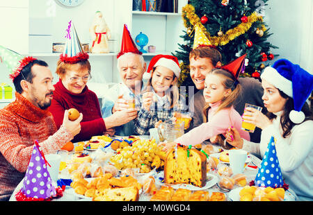 Cheerful  smiling family eating together during festive Christmas dinner - Stock Photo