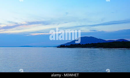 Blue cloudy sky with some orange over te Adriatic sea just after sunset, with island with trees and mountain in - Stock Photo