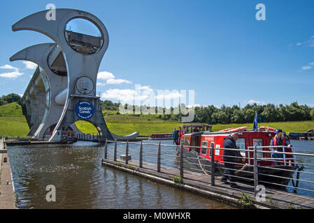 Canal boat with tourists mooring at Falkirk Wheel, rotating boat lift, Stirlingshire, Scotland, UK - Stock Photo