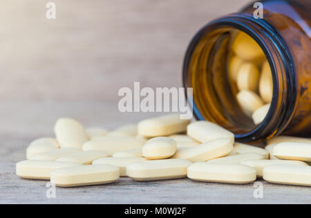 Pills or vitamin in Medicine bottles on wood background - Stock Photo