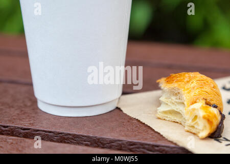 A white take-away cup and a half-eaten chocolate croissant on a table outdoors - Stock Photo